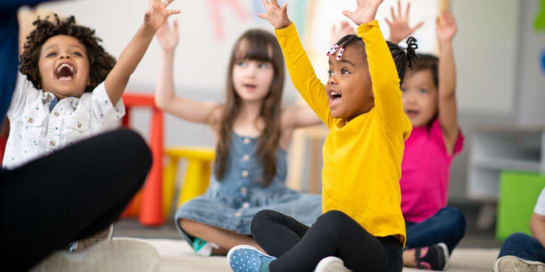 A multi-ethnic group of preschool students is sitting with their legs crossed on the floor in their classroom. The mixed-race female teacher is sitting on the floor facing the children. The happy kids are smiling and following the teacher's instructions. They have their arms raised in the air.