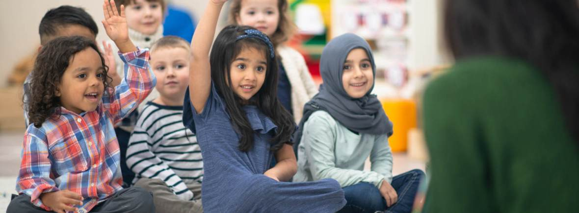A multi-ethnic group of preschool kids is indoors in their classroom. They are sitting on the floor and raising their hand to answer a question posed by their teacher while reading a story. They are all smiling.
