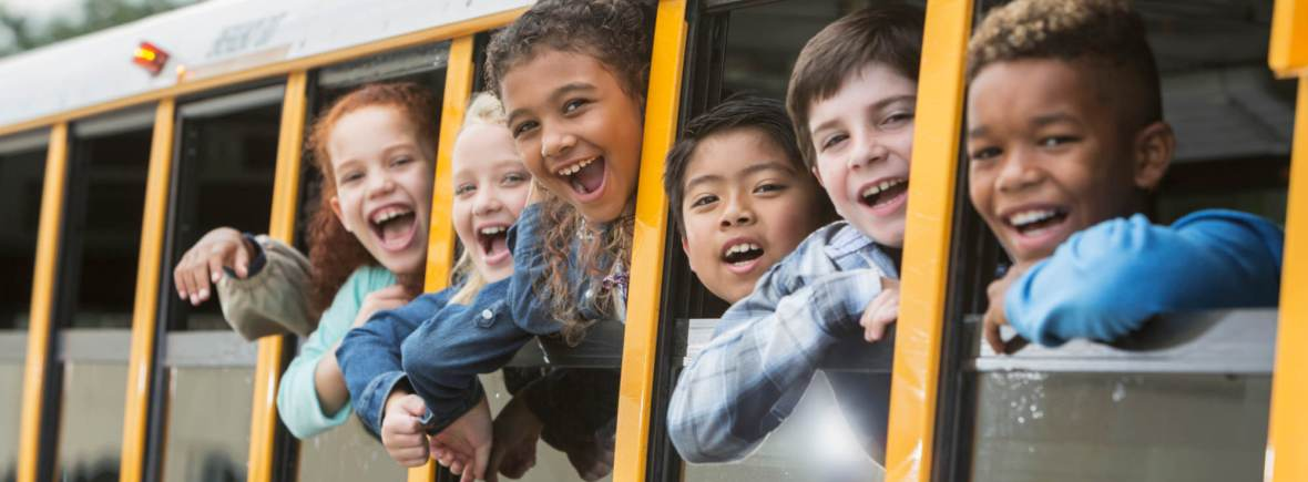 A group of six multi-ethnic elementary school students, 7 to 9 years old, on a yellow school bus, looking out the windows. The view is from outside the bus looking in.