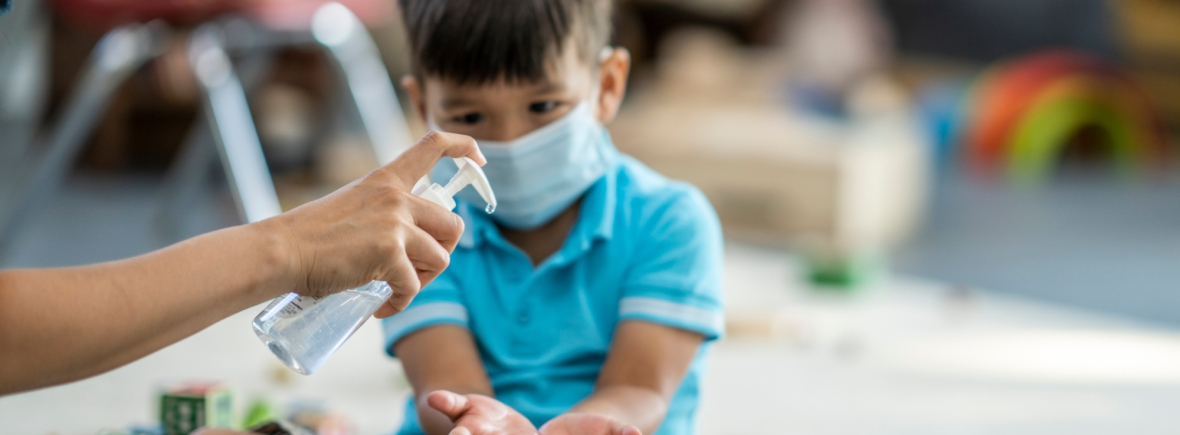 Young asian boy wearing a protective face mask sanitizes his hands while playing at daycare.