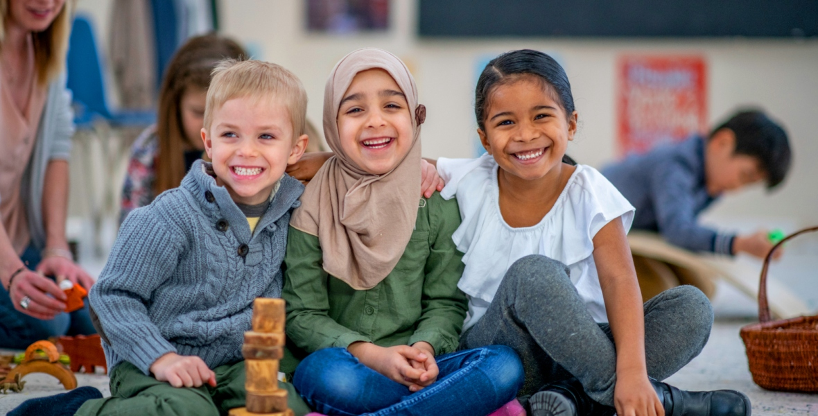A multi-ethnic group of kindergarten friends smile as they play with blocks in their classroom.